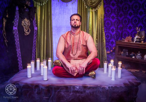 Baron Ambrosia sitting on desk with candles and smoke