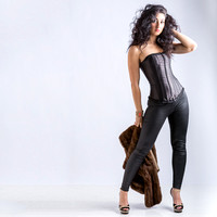 Fashion image of a young lady in the black leather pants, corset and shoes
